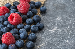 Scattered blueberries and raspberries space for text. Scattered blueberries and raspberries on jute tablecloth and chalkboard background close up, space for text royalty free stock photo