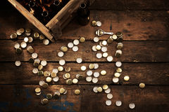 Scattered bottle tops and a crate of empty bottles Stock Photos