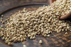 Scattered buckwheat lies in a brown clay bowl. Cooking Royalty Free Stock Photos