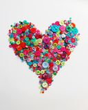 Scattered buttons in heart shape. Scattered buttons in bright colours arranged in heart shape Royalty Free Stock Photos