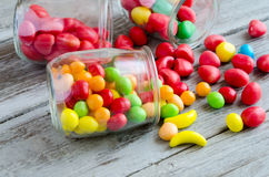 Scattered candies near jar of colorful sweets. Jar scattered with candies on table Royalty Free Stock Images