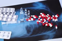 Scattered capsules, tablets, ampules and syringe on the table royalty free stock photo