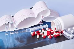 Scattered capsules, tablets, ampules and syringe on the table with cardiogram stock photo