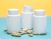 Scattered capsules with white plastic jars Stock Image