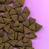 Scattered cat biscuits. Overhead view of scattered triangular brown cat biscuits on lavender background stock photos