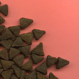 Scattered cat biscuits. Overhead view of scattered triangular cat biscuits on salmon colored background with copy space Royalty Free Stock Photo