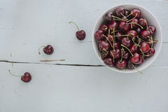 The scattered cherries in a white bowl Royalty Free Stock Image
