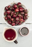 The scattered cherries in a white bowl Stock Photos