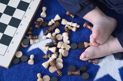 Scattered chess and children`s legs stock photo