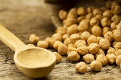Scattered chickpeas from a jute bag on old wooden background Stock Photo