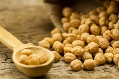 Scattered chickpeas from a jute bag on old wooden background Royalty Free Stock Photos