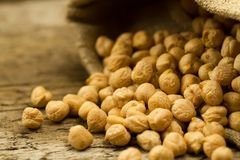 Scattered chickpeas from a jute bag on wooden background Stock Images