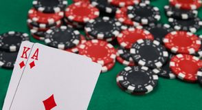 Scattered chips for betting in the casino and two game cards with a face value of 21, on the background of the green table stock image