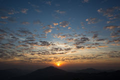 Scattered clouds sky and sunrise. Sunrise with scattered clouds sky and the dark mountain foreground Royalty Free Stock Photos