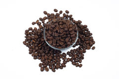 Scattered coffee beans around and within glass jug. Scattered brown coffee beans inside and around glass jug Stock Image