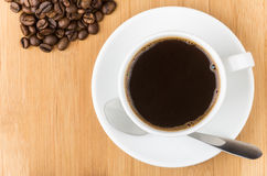Scattered coffee beans and glass cup Stock Image