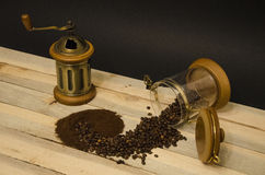 Scattered coffee beans ground coffee and manual coffee grinder on the wooden boards and on black background royalty free stock image