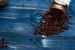 Scattered coffee beans in a jar on vintage a dark blue wooden background. Cup of coffee, bag and scoop on old rusty background royalty free stock images