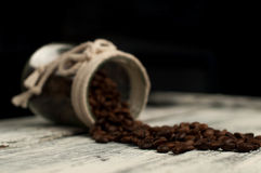 Scattered coffee beans in a jar on wood. En stock images