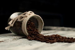 Scattered coffee beans in a jar on wood. En royalty free stock image