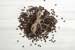 Scattered coffee beans with wool rope on light wooden surface Royalty Free Stock Image