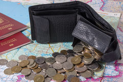 Scattered coins from a purse on a background map. Wallet and coins scattered across the map. near are two passport Royalty Free Stock Photos