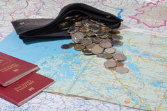 Scattered coins from a purse lying on the map. Wallet and coins scattered across the map. near are two passport Royalty Free Stock Photos