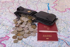 Scattered coins and purse are on the map. Wallet and coins scattered across the map. near are two passport Royalty Free Stock Image