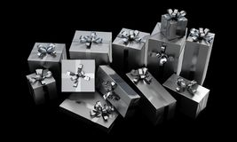 Scattered Gift Box Pile. A scattered collection of various sized gift boxes wrapped in silver paper and a silver ribbon and bow on an isolated dark studio stock photo