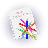 Scattered colored pencils on a white sheet notepad. Inscription happy Teachers' Day. Stock Image