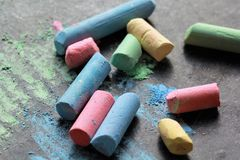 Scattered colorful crayon chalks on black boar Stock Images