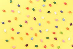 Scattered colorful jelly bean sweets on yellow background stock photography