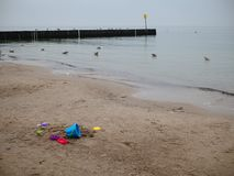 Scattered colorful toys up to the sand on the beach by the sea, nobody royalty free stock images