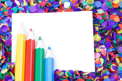 Scattered confetti background with copy space. Scattered confetti and colorful pencils, background with copy space Royalty Free Stock Photos