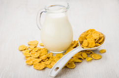 Scattered corn flakes, jug of milk and plastic spoon Stock Images