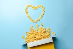 Scattered cornflakes out of box a heart shaped. Dry cereal breakfast. I love cereal. Scattered cornflakes out of box a heart shaped. Dry cereal breakfast. I royalty free stock image