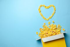 Scattered cornflakes out of box a heart shaped. Dry cereal breakfast. I love cereal. Copy space for text. Scattered cornflakes out of box a heart shaped. Dry royalty free stock photo