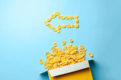 Scattered cornflakes out of the box in the shape of an arrow to the left. Dry cereal breakfast.  stock photo