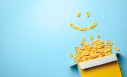 Scattered cornflakes out of the box in the shape of a smile, smiling face. Dry cereal breakfast. Copy space for text. Scattered cornflakes out of the box in the stock photo