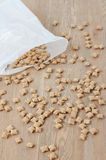 Scattered crunchy flakes. Scattered from a package crunchy flakes on the wooden table royalty free stock image