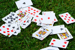 Scattered Deck of Cards. Deck of cards scattered in a field of grass Stock Photo