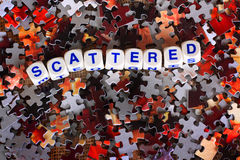 Scattered. Dice spelling out the word scattered sits on top of red and gray scattered puzzle pieces Royalty Free Stock Photo