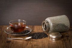 Scattered dry tea leaves with glass cup of tea Royalty Free Stock Photo