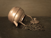 Scattered dry tea leaves and vintage teapot Stock Images