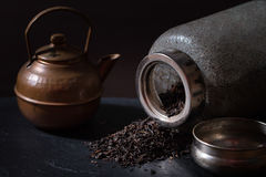 Scattered dry tea, old  jar and a vintage teapot Royalty Free Stock Photography