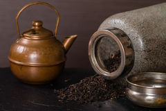 Scattered dry tea, old  jar and a vintage teapot Royalty Free Stock Image
