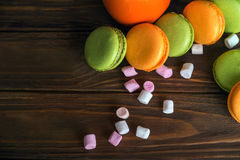 Scattered french macaroons and marshmellow in dark wooden background Stock Image