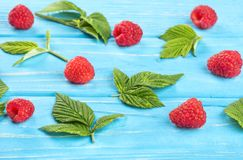 Fresh red raspberries. Scattered fresh red raspberries with leaves on a blue table Stock Photos
