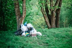 Scattered garbage in the forest. Environmental pollution, social problems royalty free stock images