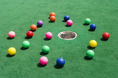 Scattered Golf Balls. A number of brightly colored golf balls scattered around the hole on a practice putting green Royalty Free Stock Images
